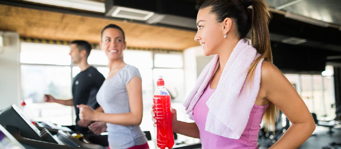women on treadmills with water bottle