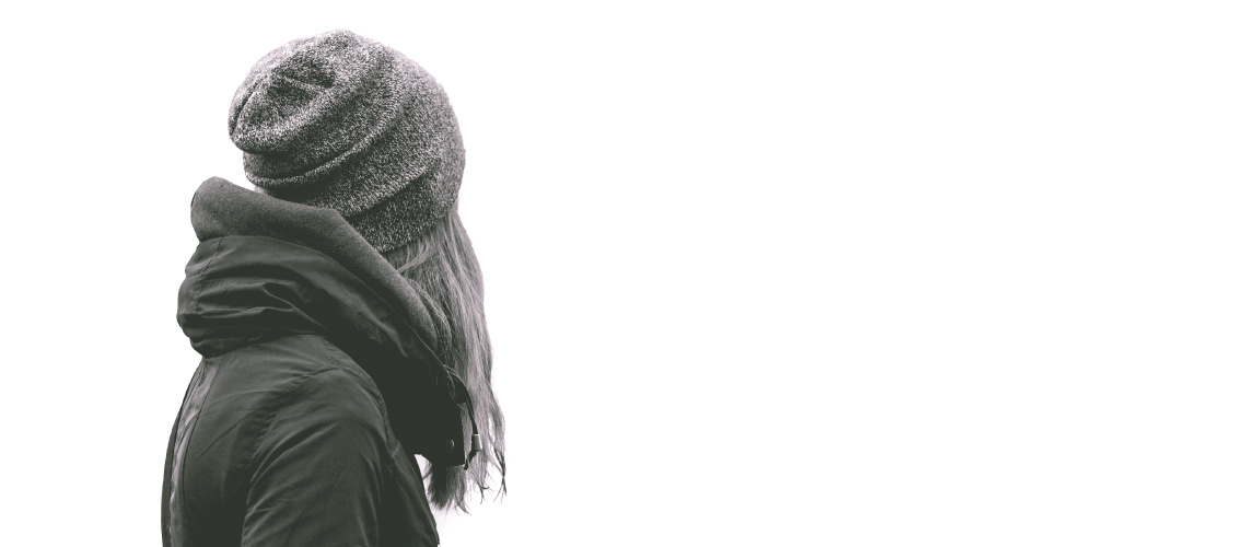 black and white photo of girl wearing hoodie and beanie looking into distance