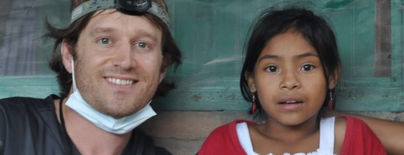 Dr. Brent Rising smiling next to young girl with black hair