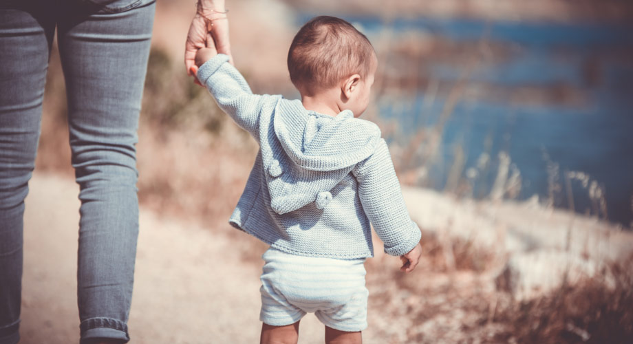 Young toddler boy holds the hand of his mother while walking along a sandy tail next to a body of water