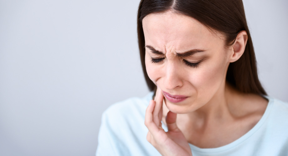 Brunette woman wearing a blue shirt cringes due to her toothache pain as she touches her cheek