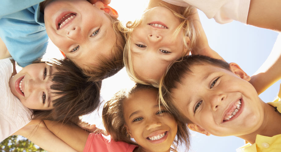 5 kids, boys and girls, looking down into the camera smiling on a sunny day